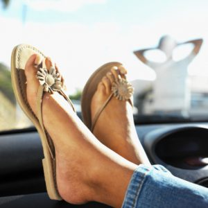 Close-up low section of young woman with legs resting on dashboard