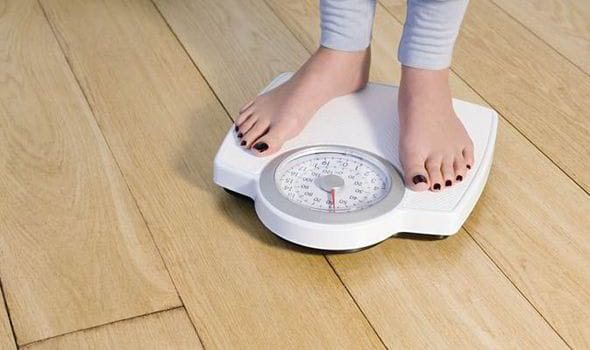 Woman-weighing-herself-on-scales-547649